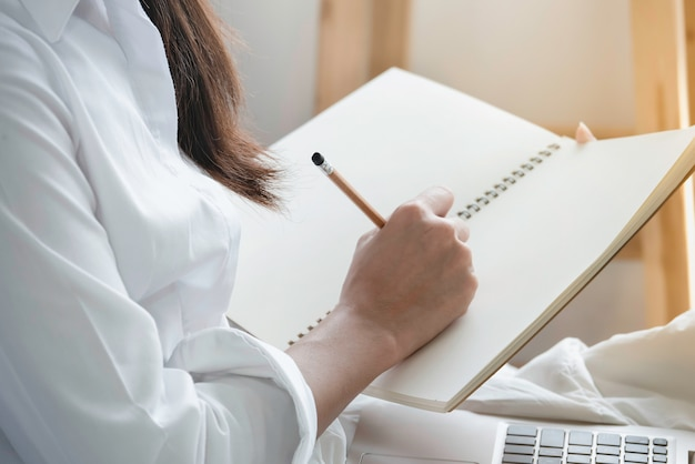 Ręka kobieta trzyma ołówkowego writing pustego notatnika w przypadkowych ubraniach.