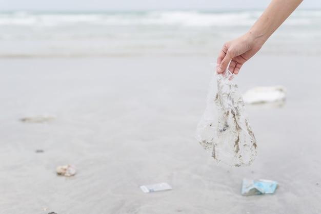 Ręka kobieta zbierając plastikowe torby do czyszczenia na plaży
