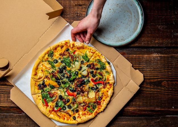 Ręka kobiety bierze śródziemnomorską pizzę z oliwkami i serem z kartonu w talerzu