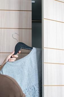 Ręka kobiety bierze szarą koszulę, szare koszule wisi w szafie