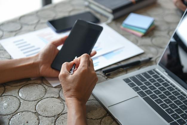 Ręka kobiety biznesu korzysta z telefonu komórkowego, aby znaleźć informacje.