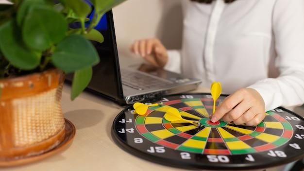 Ręka kobiety biznesu trzymając rzutkę na cel do pomyślnego celu na stole