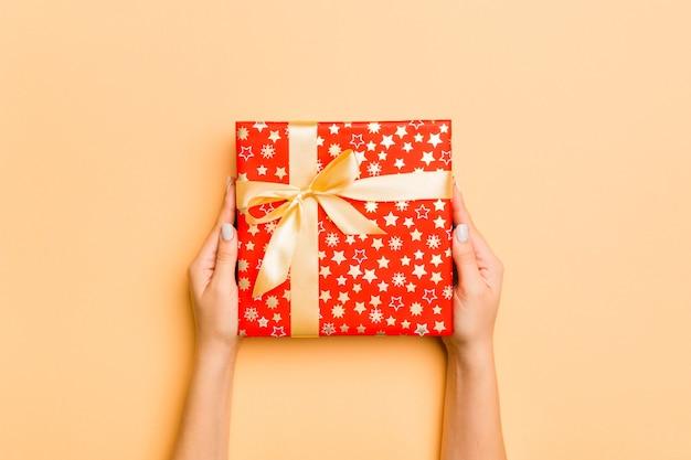 Ręka kobiety dać pudełko na prezent valentine, widok z góry.