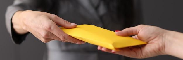 Ręka kobiety dająca kopertę innej kobiecie koncepcja korupcja i przekupstwo w koncepcji biznesowej