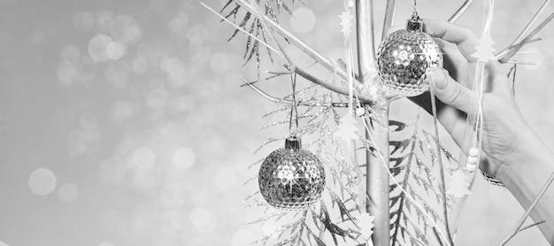 Ręka kobiety dekoruje alternatywną choinkę z suchego malowanego na srebrne drewno ze srebrnymi bombkami, błyszczącymi gałązkami, świątecznymi taśmami. kreatywny szeroki baner xmas czarno-biały. skopiuj miejsce.