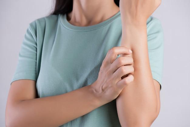 Ręka kobiety drapie swędzenie ręką w domu. pojęcie opieki zdrowotnej i medycznej.