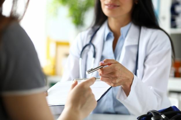 Ręka kobiety gp przechodzącej na srebrny długopis pacjenta