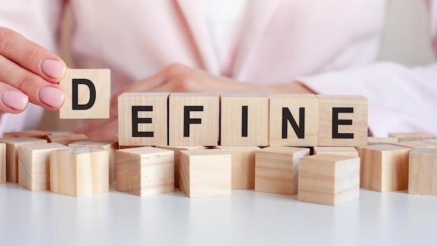 Ręka kobiety kładzie drewnianą kostkę z literą d od słowa define