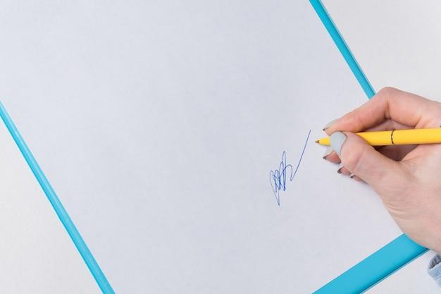 Ręka kobiety kładzie swój podpis na kartce papieru. zaloguj się w dokumencie. zamknij się, miejsce, wzór tła