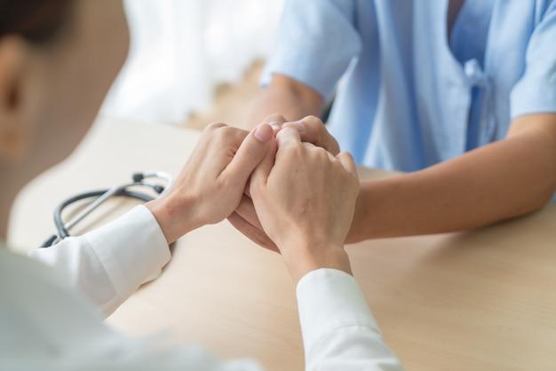 Ręka kobiety lekarka trzyma dalej jej starszego pacjenta
