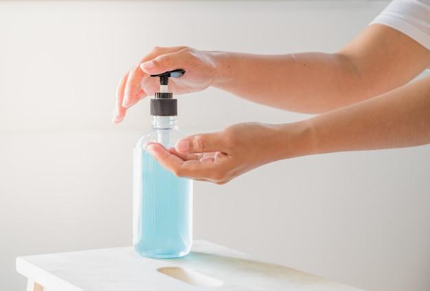Ręka kobiety mienia alkoholem gel od pompowej butelki. chroń koronawirusa (covid-19)