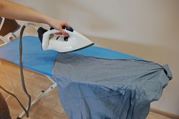 Ręka kobiety na deskę do prasowania z systemem żelazka parowego