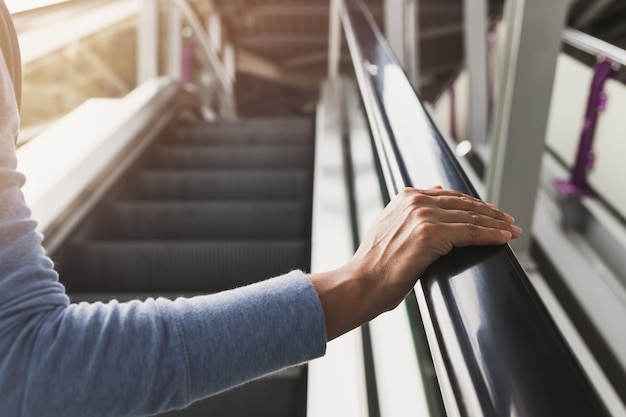 Ręka kobiety na poręczy schodów ruchomych na stacji kolejowej