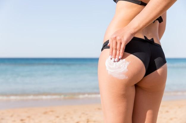 Ręka kobiety nakłada krem do opalania na jej pośladki na plaży na tle morza.