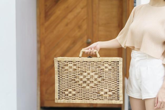 Ręka kobiety niesie wiklinową walizkę.