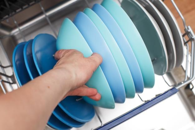 Ręka kobiety otwiera zmywarkę z czystymi naczyniami w kuchni