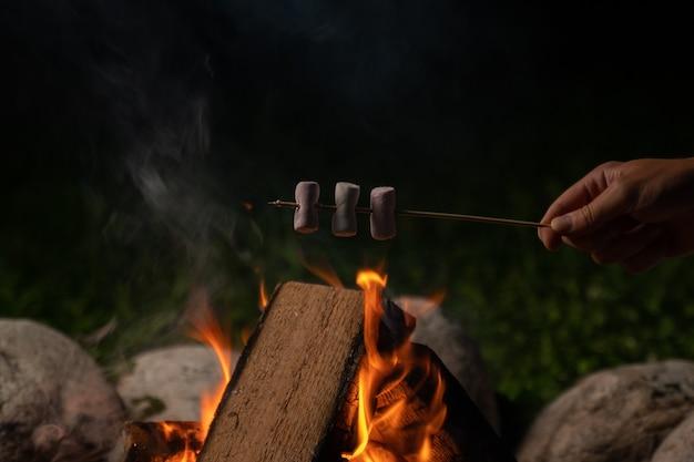Ręka kobiety piecze pianki na ognisku zbliżenie