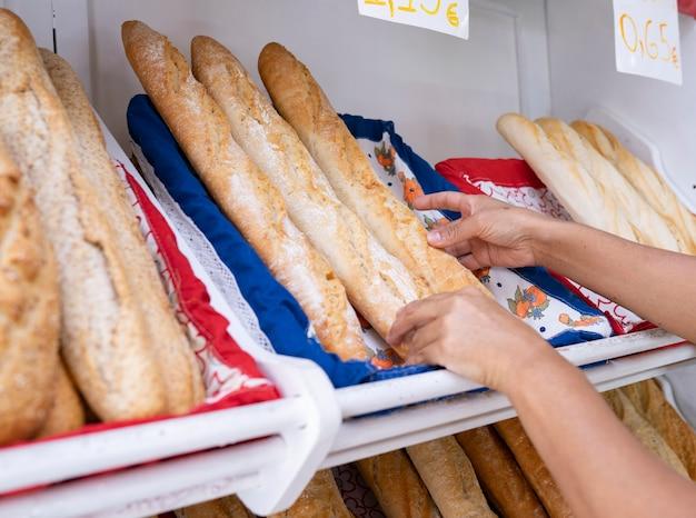 Ręka kobiety piekarza biorąca bochenek chleba