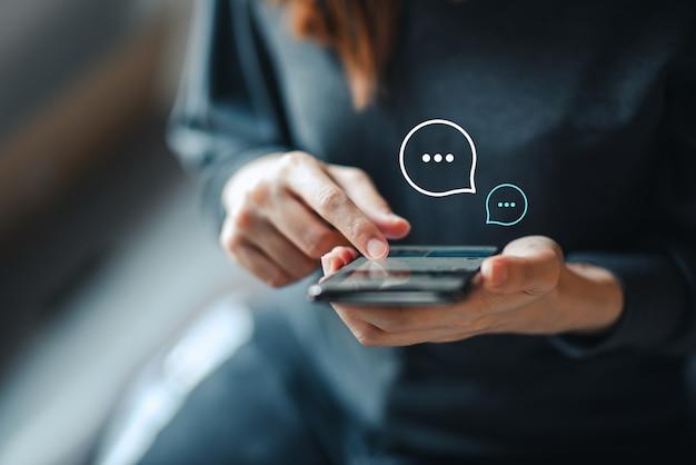 Ręka kobiety pisania na smartfonie, czat na żywo, rozmowy na temat aplikacji komunikacja cyfrowa sieć i koncepcja sieci społecznej. praca w domu.