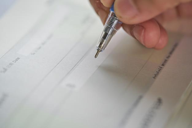 Ręka kobiety pisanie czeku, checque lub czeku.
