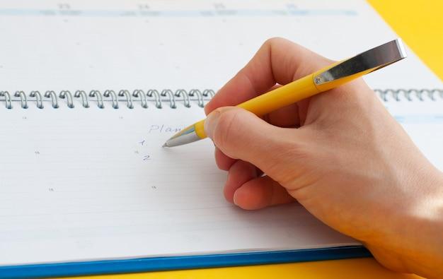 Ręka kobiety, pisząc wpisy w zeszycie. plan, 1, 2.