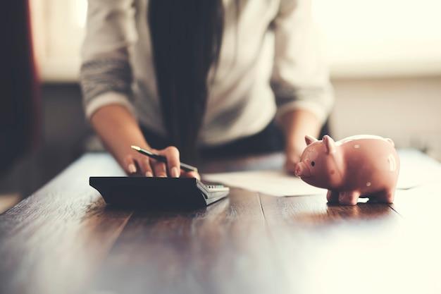 Ręka kobiety pisząca w dokumentach i używająca kalkulatora