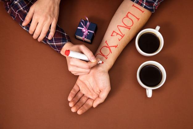 Ręka kobiety pisze czerwone litery kocham cię na dłoni mężczyzny w pobliżu dwóch filiżanek kawy na brązowo.