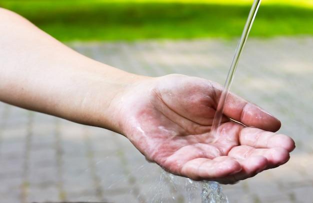 Ręka kobiety pod zimną bieżącą wodą.
