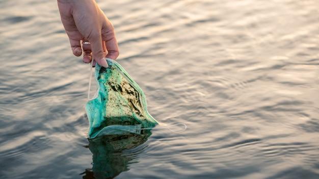 Ręka kobiety podnosząca wyrzuconą, używaną jednorazową maskę medyczną unosi się w wodach morskich. odpady tworzyw sztucznych koronawirusa zanieczyszczające środowisko. śmieci na plaży zagrażają zdrowiu oceanów.