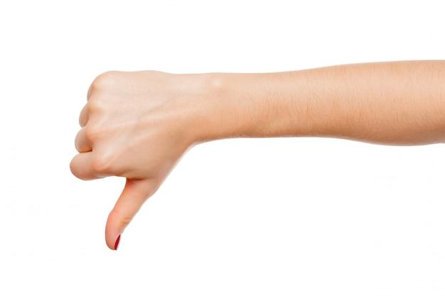 Ręka kobiety pokazuje kciuk w dół na białym tle, koncepcja negatywna