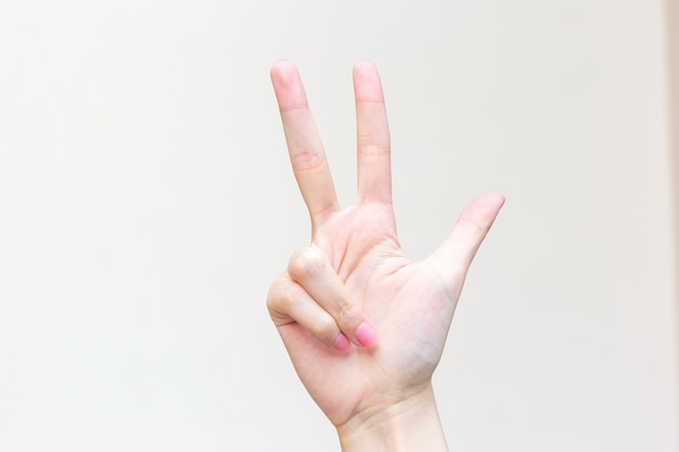 Ręka kobiety pokazuje trzy palce jako numer trzy na białym tle