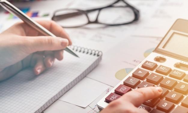 Ręka kobiety pracuje na kalkulatorze