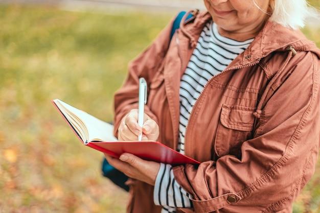 Ręka kobiety robić notatki piórem na notebooku w ogrodzie lub parku