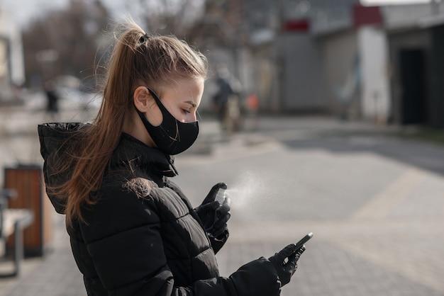 Ręka kobiety rozpyla alkohol, spray dezynfekujący na telefon komórkowy, zapobiega infekcji wirusem covid-19, zanieczyszczeniu zarazkami lub bakteriami, wyciera telefon lub czyści telefon w celu wyeliminowania, wybuchu koronawirusa