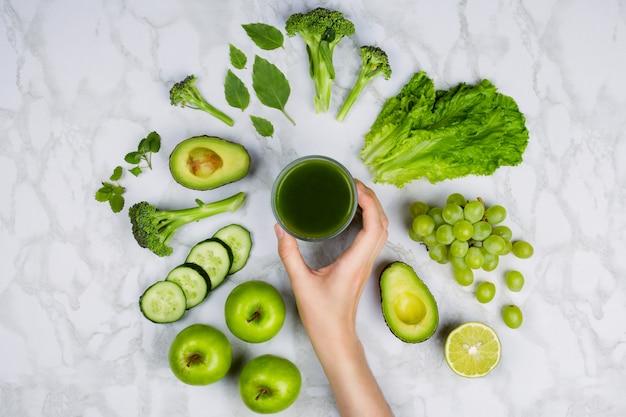 Ręka kobiety sięgają po zielony sok