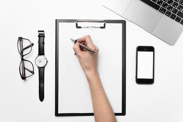 Ręka kobiety trzyma długopis i pisze na czystym arkuszu papieru. białe biurko z laptopem, telefonem i materiałami eksploatacyjnymi.