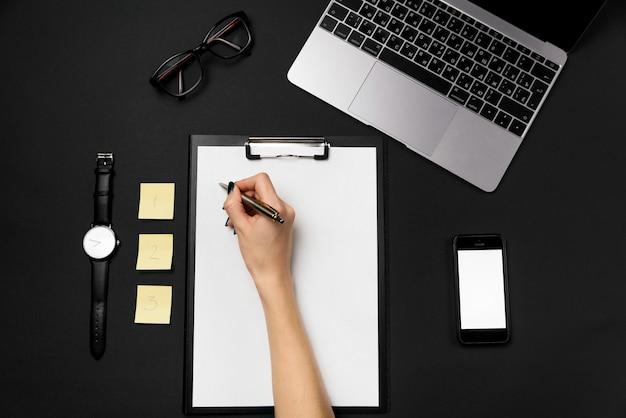 Ręka kobiety trzyma długopis i pisze na czystym arkuszu papieru. czarne biurko z laptopem, telefonem i materiałami eksploatacyjnymi. żółte papiery na notatki z jedną, dwiema, trzema liczbami.