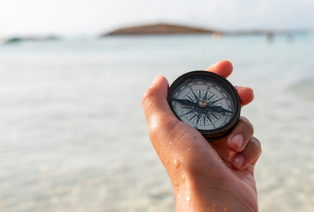 Ręka kobiety trzyma kompas na plaży