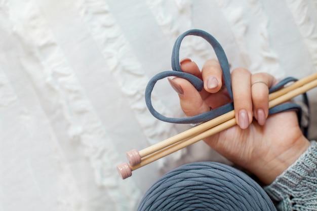 Ręka kobiety trzyma niebieską włóczkę z dzianiny, składając ją w kształt serca. koncepcja miłości do dziewiarstwa i rękodzieła.