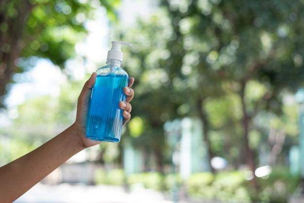Ręka kobiety trzyma niebieski żel do rąk z alkoholem dezynfekującym do ochrony przed koronawirusem