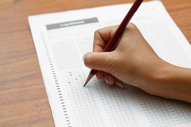 Ręka kobiety trzyma ołówek na standaryzowanej formie testowej z odpowiedziami bąblującymi wewnątrz i ołówkiem, ostrość o