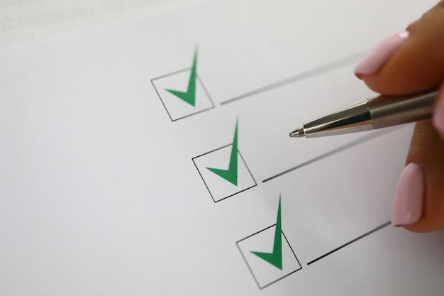Ręka kobiety trzyma pióro i zaznacza zielone znaczniki wyboru w dokumencie.