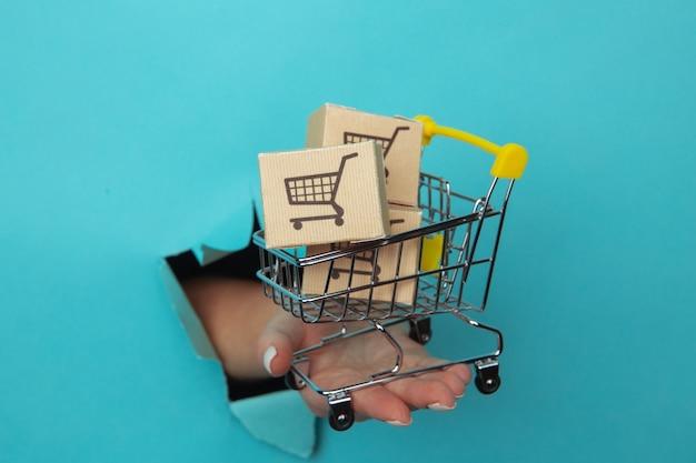 Ręka kobiety trzyma przez otwór mini wózek na zakupy spożywcze na niebieskim papierze