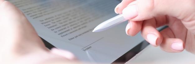 Ręka kobiety trzyma rysik i umieszcza podpis elektroniczny w umowie na tablecie