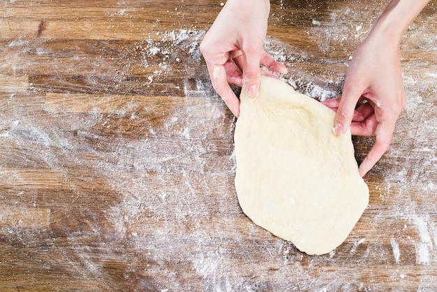 Ręka kobiety trzyma spłaszczone ciasto na drewnianym biurku