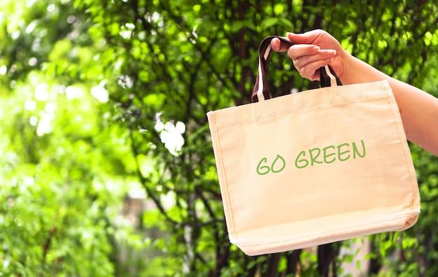 Ręka kobiety trzyma torbę wielokrotnego użytku z zieloną koncepcją bez plastiku