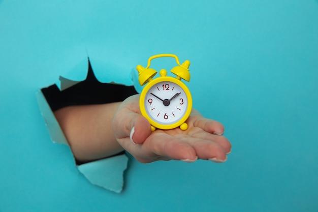 Ręka kobiety trzyma żółty budzik przez niebieski otwór papieru