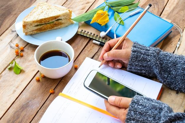 Ręka kobiety trzymającej telefon komórkowy do pracy biznesowej i śniadanie