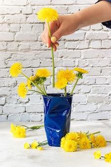 Ręka kobiety układa mlecze w niebieskiej filiżance