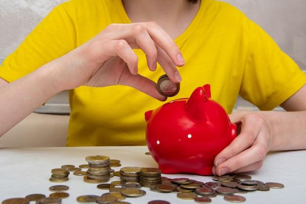 Ręka kobiety umieścić monety pieniądze w skarbonka do oszczędzania pieniędzy i koncepcji finansowej, kilka monet na stole.